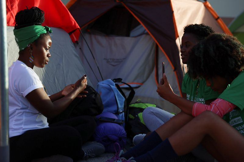 Abortion rights activists sit outside tents set up in front of the National Palace during a protest to pressure parliament over a proposed reform to the penal code that could end the total ban on abortion, in Santo Domingo