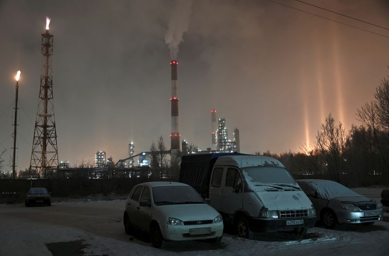 FILE PHOTO: Vehicles covered with snow and hoarfrost are parked near a local oil refinery in Omsk