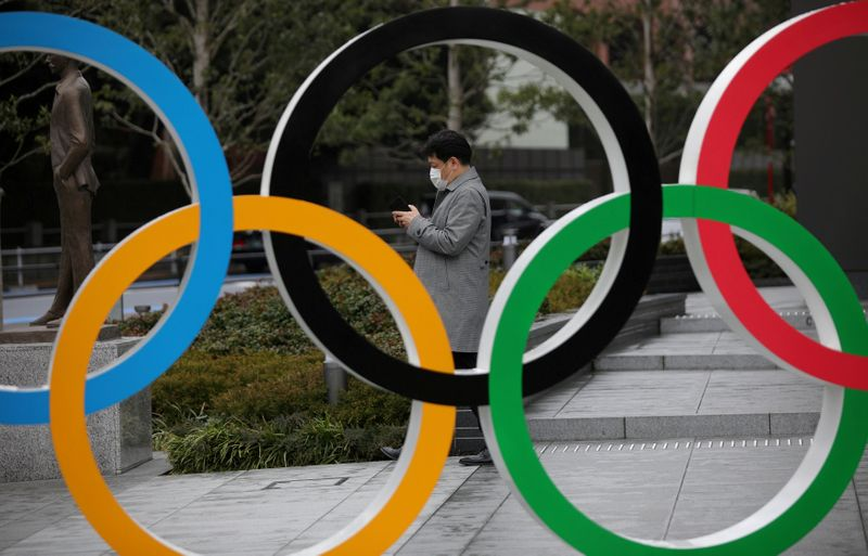 FILE PHOTO: Man looks at his mobile phone next to The Olympic rings in front of the Japan Olympics Museum in Tokyo