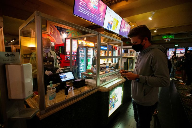 FILE PHOTO: A moviegoer shops at concession stands retrofitted with plexiglass partitions before the movie