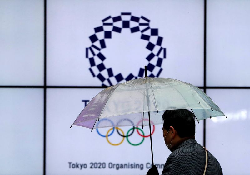 FILE PHOTO: A man wearing a protective face mask walks past in front of a display showing the logo of Tokyo 2020 Olympic Games, amid the coronavirus disease (COVID-19) outbreak in Tokyo