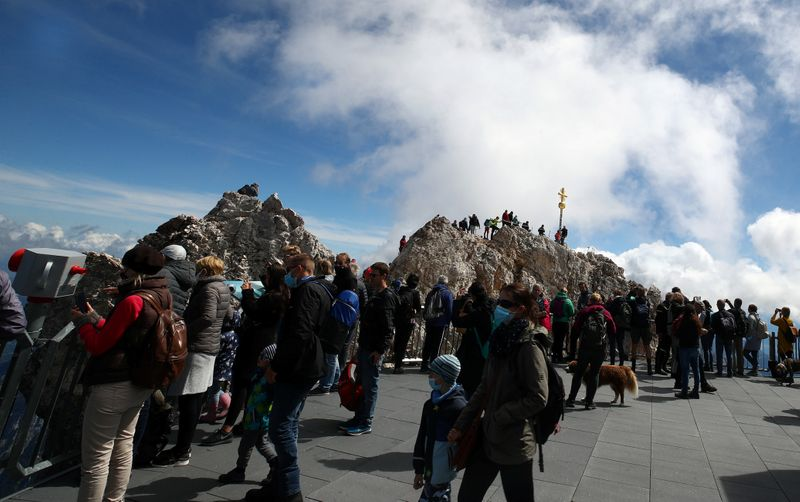 People queue to reach the summit cross on top of the highest German mountain, the Zugspitze, in Grainau
