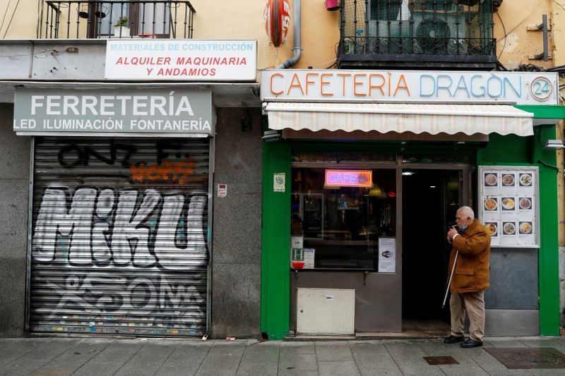 FILE PHOTO: A man smokes a cigarette next to a closed business during the coronavirus disease (COVID-19) outbreak in Madrid