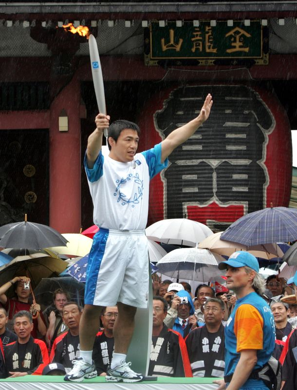 OLYMPIC JUDO GOLD MEDALIST JAPAN'S TOSHIHIKO KOGA HOLDS OLYMPIC TORCH AT SENSOJI TEMPLE IN TOKYO.