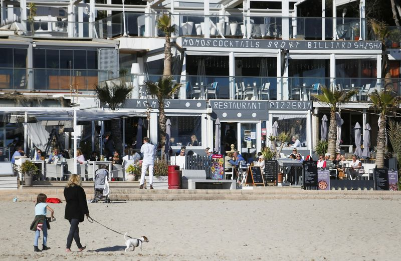 FILE PHOTO: Tourists chill and take drinks in terrace bars in Paguera beach