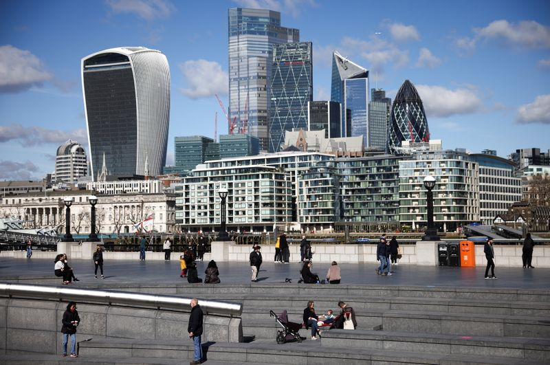 The City of London financial district can be seen as people walk along the south side of the River Thames, amid the coronavirus disease (COVID-19) outbreak in London