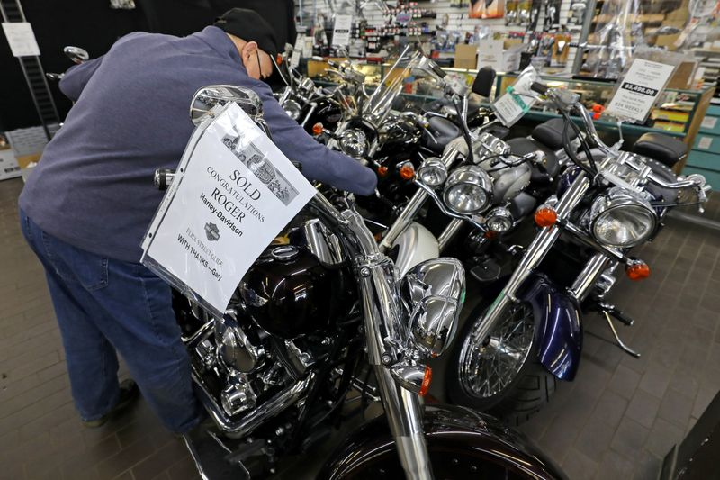 Gary Haines places a SOLD sign on a Harley Davidson motorcycle in Toronto
