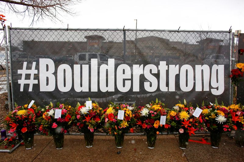 People leave flowers at the site of a mass shooting at King Soopers grocery store in Boulder