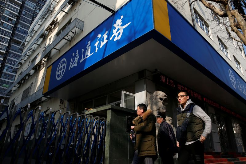 People walk past a branch of Haitong Securities, in Shanghai