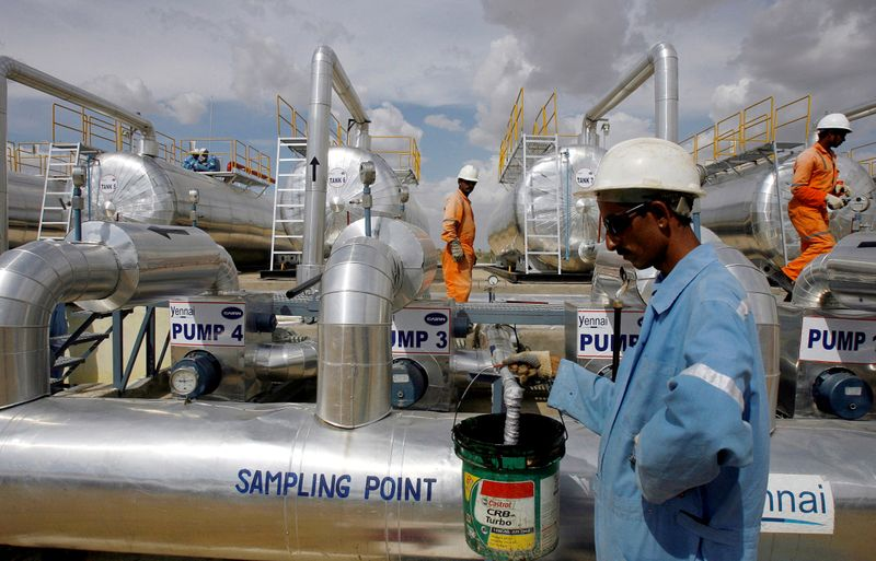 FILE PHOTO: Cairn India employees work at a storage facility for crude oil at Mangala oil field at Barmer in the desert Indian state of Rajasthan