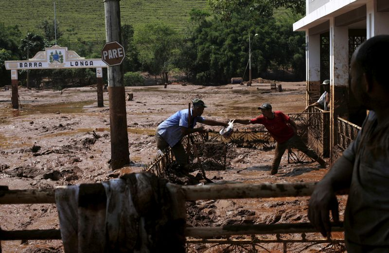 FILE PHOTO: Men take out a bag from a house flooded with mud after a dam owned by Vale SA and BHP Billiton Ltd burst, in Barra Longa