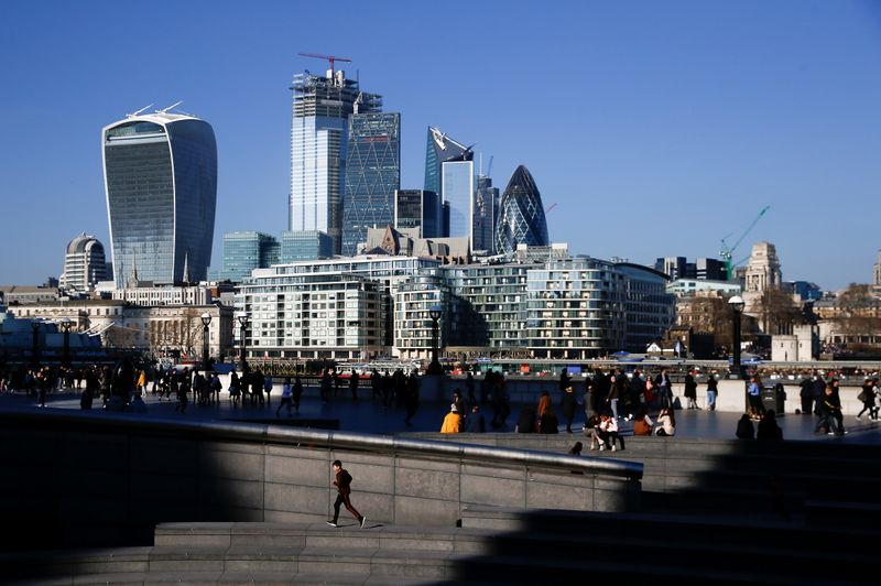 The financial district can be seen as a person runs in the sunshine on London's south bank