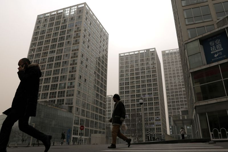 FILE PHOTO: People walk past an office and commercial complex in Beijing's Central Business District (CBD)