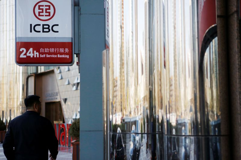 Man walks past a branch of Industrial and Commercial Bank of China (ICBC) in Beijing