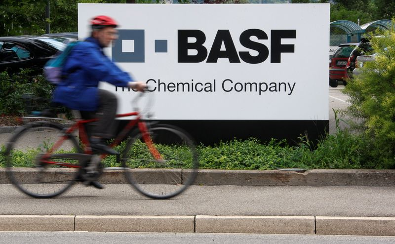 FILE PHOTO: A cyclist rides his bike bast the entrance of a BASF plant in Schweizerhalle, Switzerland