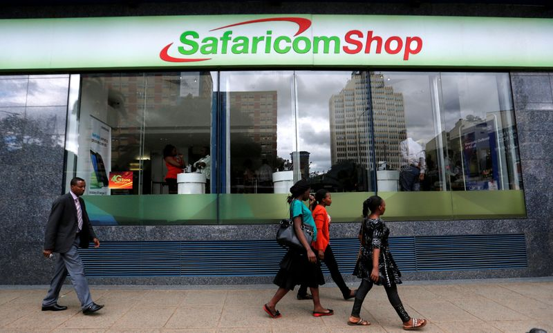 FILE PHOTO: Pedestrians walk past a mobile phone care centre operated by Kenyan's telecom operator Safaricom in the central business district of Kenya's capital Nairobi