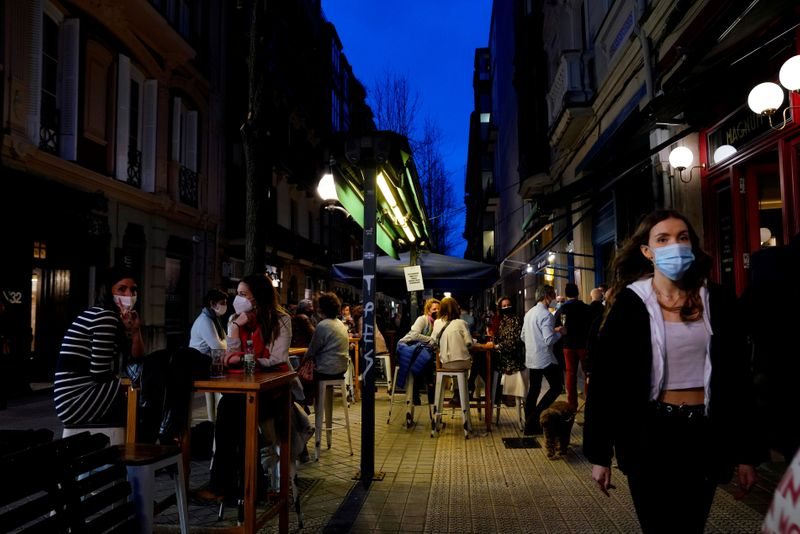 FILE PHOTO: People wearing protective masks walk past bar customers after bars reopened in Spain's Basque Country, amid the coronavirus disease (COVID-19) outbreak, in Bilbao