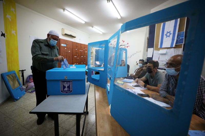 An Arab-Israeli man casts his ballot as he votes in Israel's general election, in Kafr Manda, northern Israel