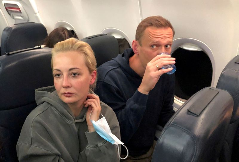 FILE PHOTO: Russian opposition leader Alexei Navalny and his wife Yulia Navalnaya are seen on board a plane during a flight from Berlin to Moscow