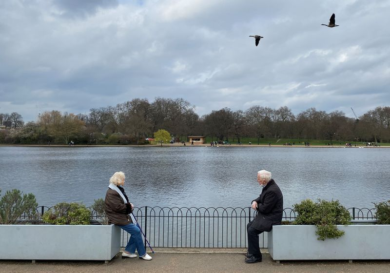 Two people are seen socially-distancing as they chat together in Hyde Park, London