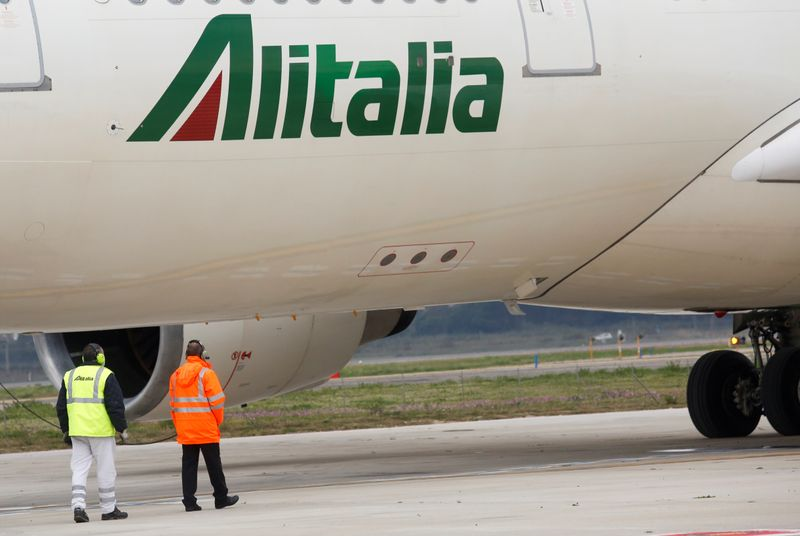 FILE PHOTO: Two workers are seen next to an Alitalia plane at Fiumicino airport in Rome, Italy