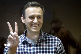 FILE - In this Saturday, Feb. 20, 2021 file photo, Russian opposition leader Alexei Navalny gestures as he stands behind a grass of the cage in the Babuskinsky District Court in Moscow, Russia. Russian opposition leader Alexey Navalny was transported to a prison 100km away from Moscow. Navalny was taken to a prison in Pokrov city after Moscow city court rejected appeal against his prison sentence on Saturday, Feb. 27, 2021. (AP Photo/Alexander Zemlianichenko, File)
