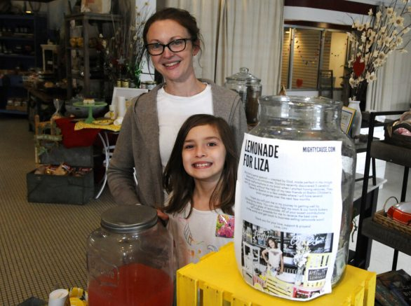 Elizabeth Scott and her 7-year-old daughter Liza Scott, who is running a lemonade stand to help fund her own brain surgery, are shown at the woman's bakery in Homewood, Ala., on Tuesday, March 2, 2021. Elizabeth Scott said the family has good health insurance, but expenses are still high and the girl wanted to help out. The child was diagnosed with brain malformations following seizures earlier this year, her mother said. (AP Photo/Jay Reeves)