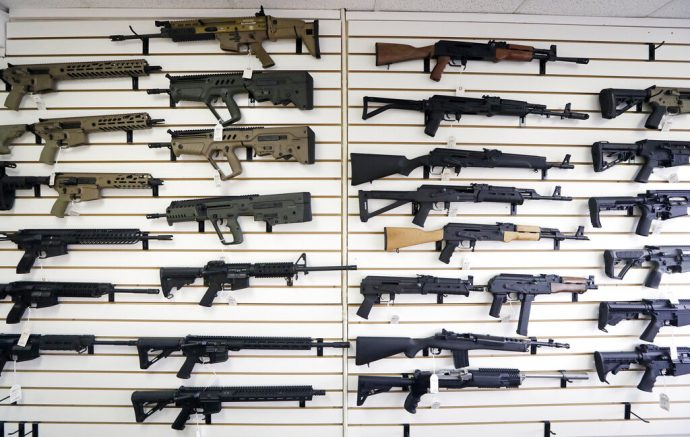 FILE - In this Oct. 2, 2018, file photo, semi-automatic rifles fill a wall at a gun shop in Lynnwood, Wash. With Democrats controlling the presidency and Congress, Republican state lawmakers concerned about the possibility of new federal gun control laws aren't waiting to react. Legislation in at least a dozen states seeks to nullify any new restrictions, such as ammunition limits or a ban on certain types of weapons. (AP Photo/Elaine Thompson, File)