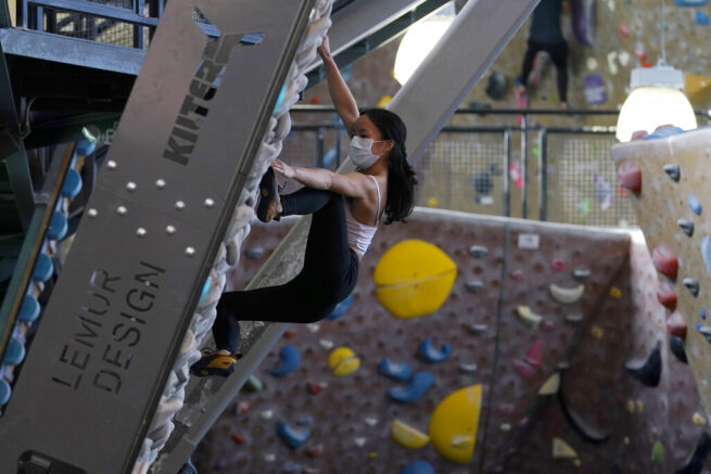 Gen Til wears a protective face mask while working out at Planet Granite climbing gym during the coronavirus pandemic in San Francisco, Thursday, March 4, 2021. The gym opened today to allow ten percent capacity. (AP Photo/Jeff Chiu)