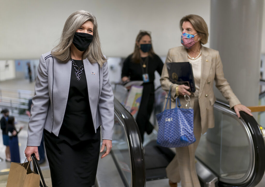 Sen. Joni Ernst, R-Iowa, left, and Sen. Shelley Moore Capito, R-W.Va., head to the chamber as the Senate holds a voting marathon on the Democrats' $1.9 trillion COVID-19 relief bill that's expected to end with the chamber's approval of the measure, at the Capitol in Washington, Friday, March 5, 2021. (AP Photo/J. Scott Applewhite)