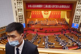 A security officials stands guard after a plenary session of China's National People's Congress (NPC) the Great Hall of the People in Beijing, Monday, March 8, 2021. (AP Photo/Sam McNeil)