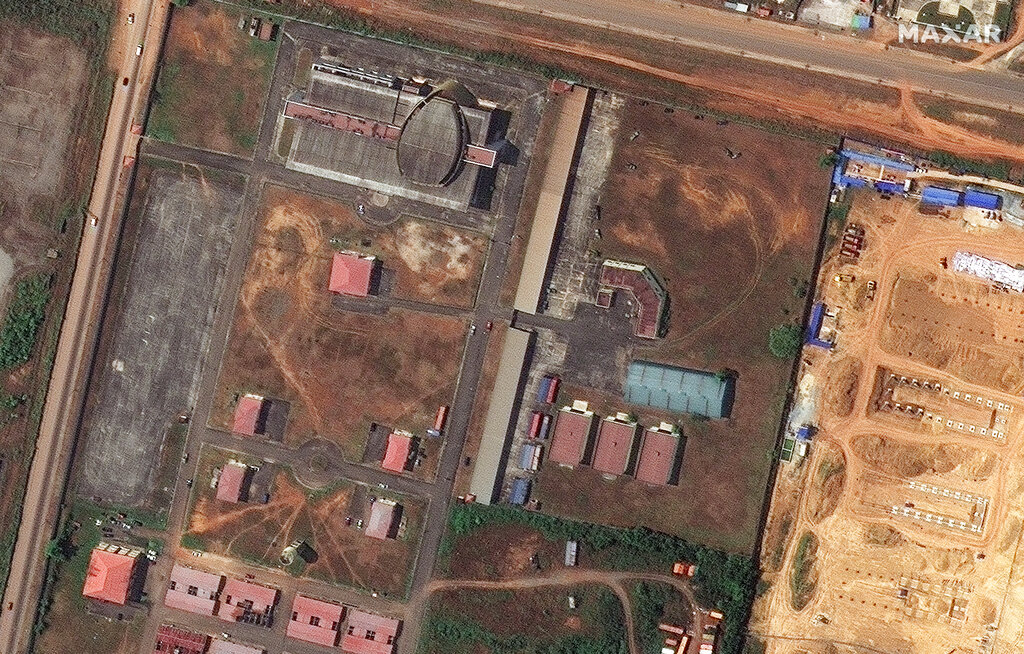 This handout satellite photo provided by Maxar Technologies shows the storage buildings before the explosion, in Bata, Equatorial Guinea, Aug. 7, 2020. The government of Equatorial Guinea says the death toll from a series of explosions at a military barracks has risen by dozens to at least 98 killed after more bodies were recovered. The blasts on Sunday in the neighborhood of Mondong Nkuantoma in the coastal city of Bata also wounded more than 600 people. (Maxar Technologies via AP)