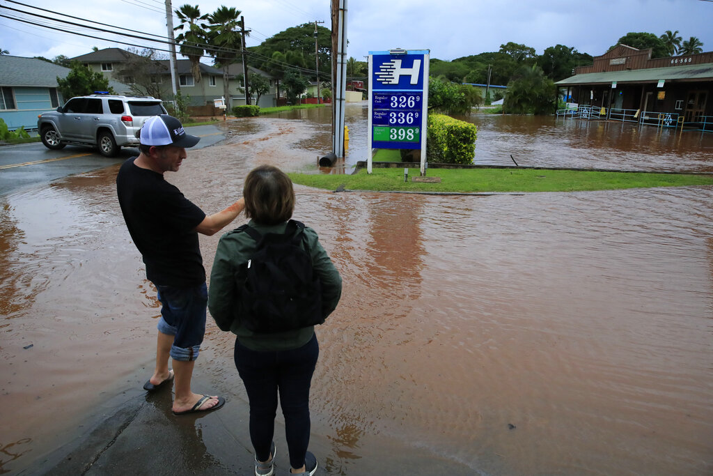 People stand at the edge of floodwaters along Haleiwa Road on Tuesday, March 9, 2021, in Haleiwa, Hawaii. Torrential rains have inundated parts of Hawaii for the past several days. (Jamm Aquino/Honolulu Star-Advertiser via AP)