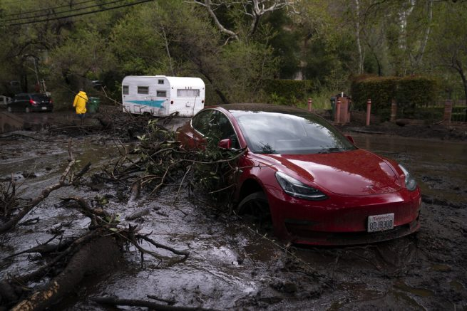 A vehicle is caught up in a mudslide in Silverado Canyon, Calif., Wednesday, March 10, 2021. A Pacific storm brought more much-needed rain and snow to California on Wednesday at the tail-end of a largely dry winter. Winter storm warnings were in effect in the southern Cascades, down the length of the Sierra Nevada and the mountains of Southern California, the National Weather Service said. (AP Photo/Jae C. Hong)
