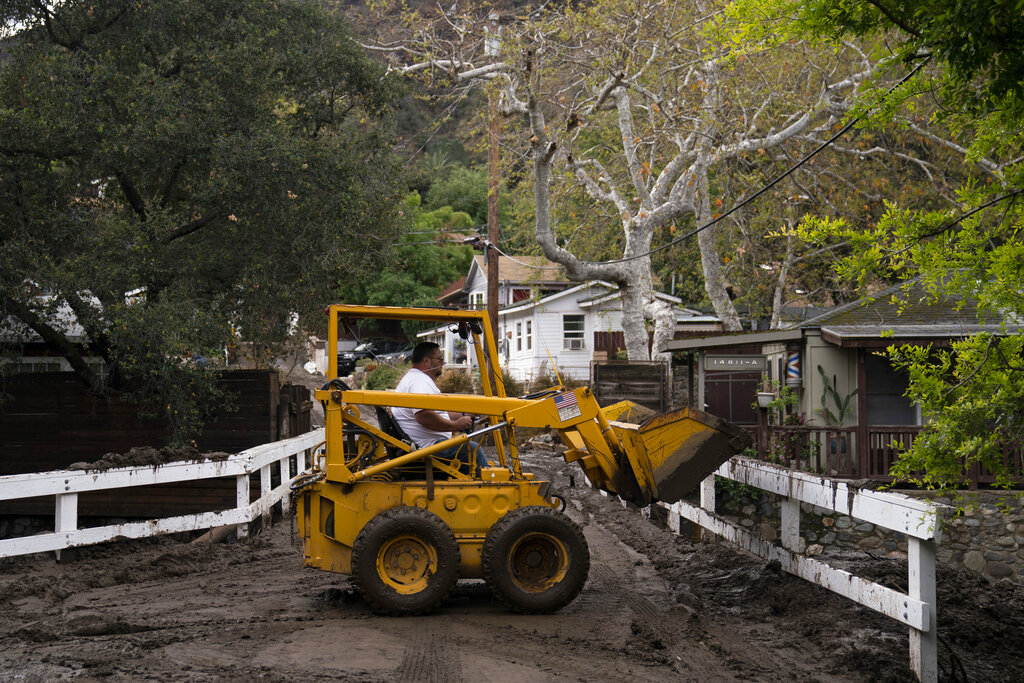 Loader operator clears debris and mud from a road after mudslides in Silverado Canyon, Calif., Wednesday, March 10, 2021. A Pacific storm brought more much-needed rain and snow to California on Wednesday at the tail-end of a largely dry winter. Winter storm warnings were in effect in the southern Cascades, down the length of the Sierra Nevada and the mountains of Southern California, the National Weather Service said. (AP Photo/Jae C. Hong)