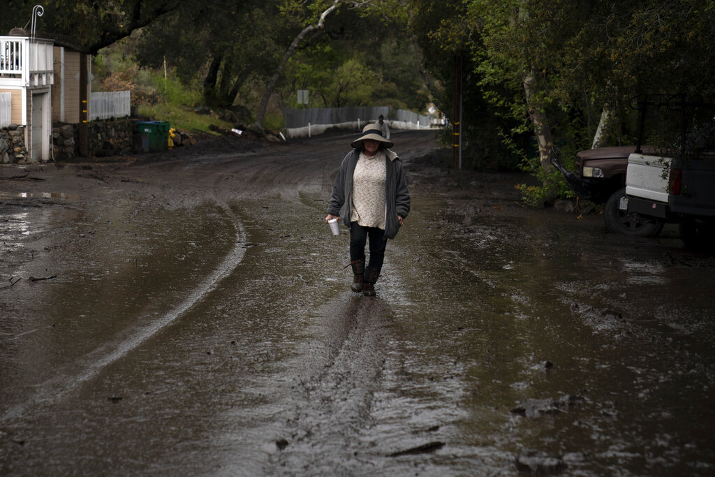 A woman walk along the street covered in mud after a mudslide swept through the neighborhood in Silverado Canyon, Calif., Wednesday, March 10, 2021. A Pacific storm brought more much-needed rain and snow to California on Wednesday at the tail-end of a largely dry winter. Winter storm warnings were in effect in the southern Cascades, down the length of the Sierra Nevada and the mountains of Southern California, the National Weather Service said. (AP Photo/Jae C. Hong)