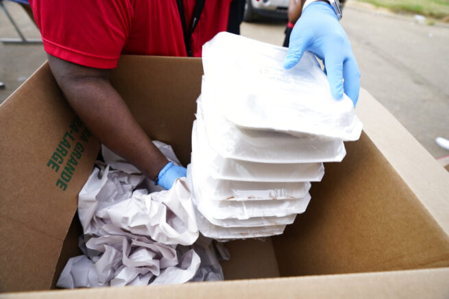 Provine High School student Joseph Anthony gathers prepared meals that are to be distributed along with bottled water to west Jackson, Miss., residents, Thursday, March 11, 2021. The Jackson Public School District set up sites at several schools to help residents who still are under a boil water notice. Over 400 meals were given out as well as cases of water that school officials hope will be used for cooking since although water pressure has generally returned to much of the city, the water has yet to pass water quality tests. (AP Photo/Rogelio V. Solis)