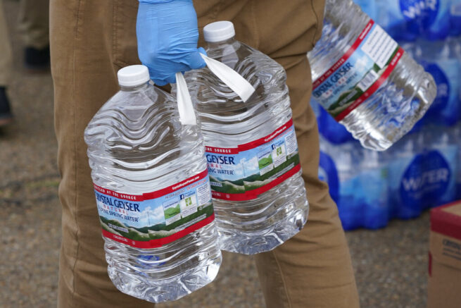 The faculty and students at Provine High School served prepared meals and distributed bottled water to residents in west Jackson, Miss., Thursday, March 11, 2021. The Jackson Public School District set up sites at several schools to help residents who still are under a boil water notice. Over 400 meals were given out as well as cases of water that school officials hope will be used for cooking since although water pressure has generally returned to much of the city, the water has yet to pass water quality tests. (AP Photo/Rogelio V. Solis)