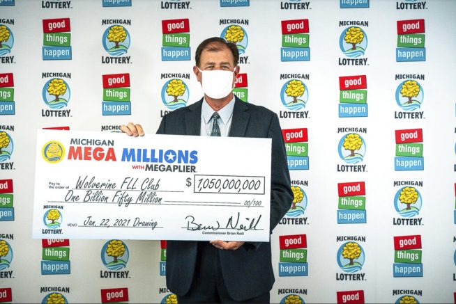 In this Feb. 26, 2021, photo provided by the Michigan Lottery, attorney Kurt Panouses poses with a check on behalf of the winners of a Mega Millions lottery jackpot in Lansing, Mich. Four people in a suburban Detroit lottery club have won a $1.05 billion Mega Millions lottery jackpot and will share $557 million after taxes. Officials made the announcement Friday, March 12, 2021, nearly two months after the Jan. 22, drawing.(Michigan Lottery via AP)
