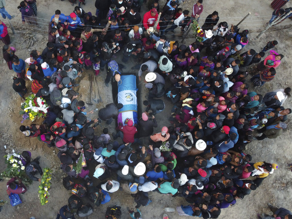 People lower the remains of Elfego Miranda Diaz into a grave, one of the Guatemalan migrants who was killed near the U.S.-Mexico border in January, at a cemetery in Comitancillo, Guatemala, Saturday, March 13, 2021. Thousands of residents of this Guatemalan town turned out Friday night amid tears and applause to receive the remains of 16 of their own, found piled in a charred pickup truck in Camargo, across the Rio Grande from Texas. (AP Photo/Moises Castillo)