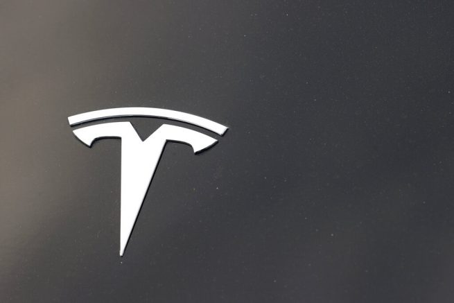The company logo is seen on the hood of an unsold Tesla at a dealership late Sunday, Aug. 9, 2020, in Littleton, Colo. On Monday, March 15, 2021, the U.S. government's highway safety agency said it is sending a team to Detroit to investigate a crash involving a Tesla that drove beneath a semitrailer. (AP Photo/David Zalubowski)
