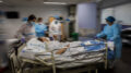 """FILE - In this Feb. 17, 2021, file photo, a COVID-19 patient is transferred to the """"red zone,"""" an area reserved for treating those suffering from COVID-19, in the Severo Ochoa Hospital in Leganes on the outskirts of Madrid, Spain. Optimism is spreading in the U.S. as COVID-19 deaths plummet and states ease restrictions and open vaccinations to younger adults. But across Europe, dread is setting in with another wave of infections that is closing schools and cafes and bringing new lockdowns. (AP Photo/Bernat Armangue, File)"""