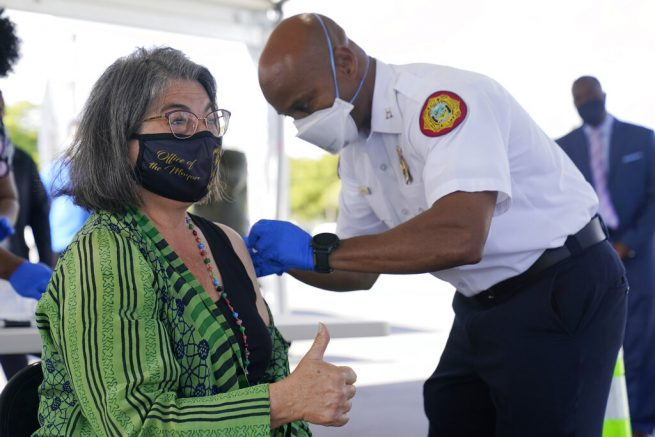 Miami-Dade County Mayor Daniella Levine Cava gives a thumbs up after getting her first dose of Pfizer's COVID-19 vaccine from Capt. Will Hall, COVID-19 Vaccine Branch Director for the county, Wednesday, March 17, 2021, at the Miami-Dade County Tropical Park COVID-19 vaccination site in Miami. (AP Photo/Wilfredo Lee)