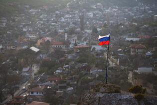 "FILE - In this March 28, 2014 file photo, a Russian national flag flies on a hilltop near the city of Bakhchysarai, Crimea. The Group of Seven major industrialized countries on Thursday March 18, 2021, issued a strong condemnation of what it called Russia's ongoing ""occupation"" of the Crimean Peninsula, seven years after Moscow annexed it from Ukraine. (AP Photo/Pavel Golovkin, File)"