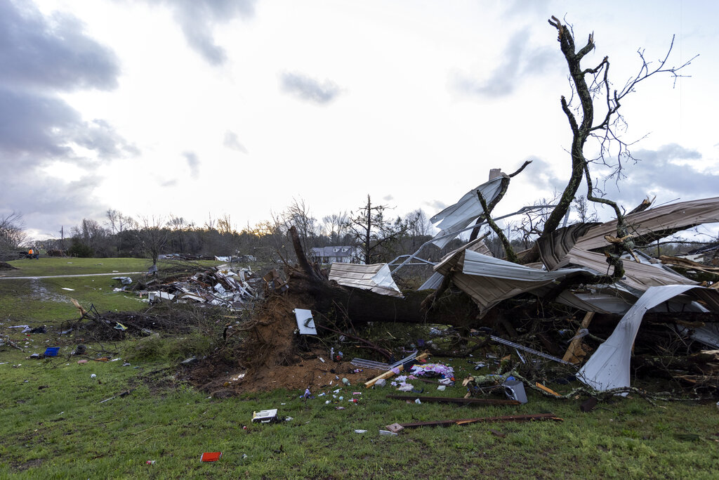 The sun rises over weather-damaged properties at the intersection of County Road 24 and 37 in Clanton, Ala., following a large outbreak of severe storms across the southeast, Thursday, March 18, 2021. Possible tornadoes knocked down trees, toppled power lines and damaged homes in multiple locations across the state of Alabama. (AP Photo/Vasha Hunt)