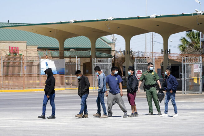 Migrants who were caught trying to sneak into the United States are led by a U.S. Customs and Border Protection agent, second from right, at the McAllen-Hidalgo International Bridge while being deported to Reynosa, Mexico, Thursday, March 18, 2021, in Hidalgo, Texas. A surge of migrants on the Southwest border has the Biden administration on the defensive. The head of Homeland Security acknowledged the severity of the problem Tuesday but insisted it's under control and said he won't revive a Trump-era practice of immediately expelling teens and children. (AP Photo/Julio Cortez)