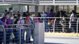 Travelers, left, waiting in line to cross a customs area into the United States at the McAllen-Hidalgo International Bridge look on as a group of migrants, right, are deported to Reynosa, Mexico, Thursday, March 18, 2021, in Hidalgo, Texas. A surge of migrants on the Southwest border has the Biden administration on the defensive. The head of Homeland Security acknowledged the severity of the problem Tuesday but insisted it's under control and said he won't revive a Trump-era practice of immediately expelling teens and children. (AP Photo/Julio Cortez)