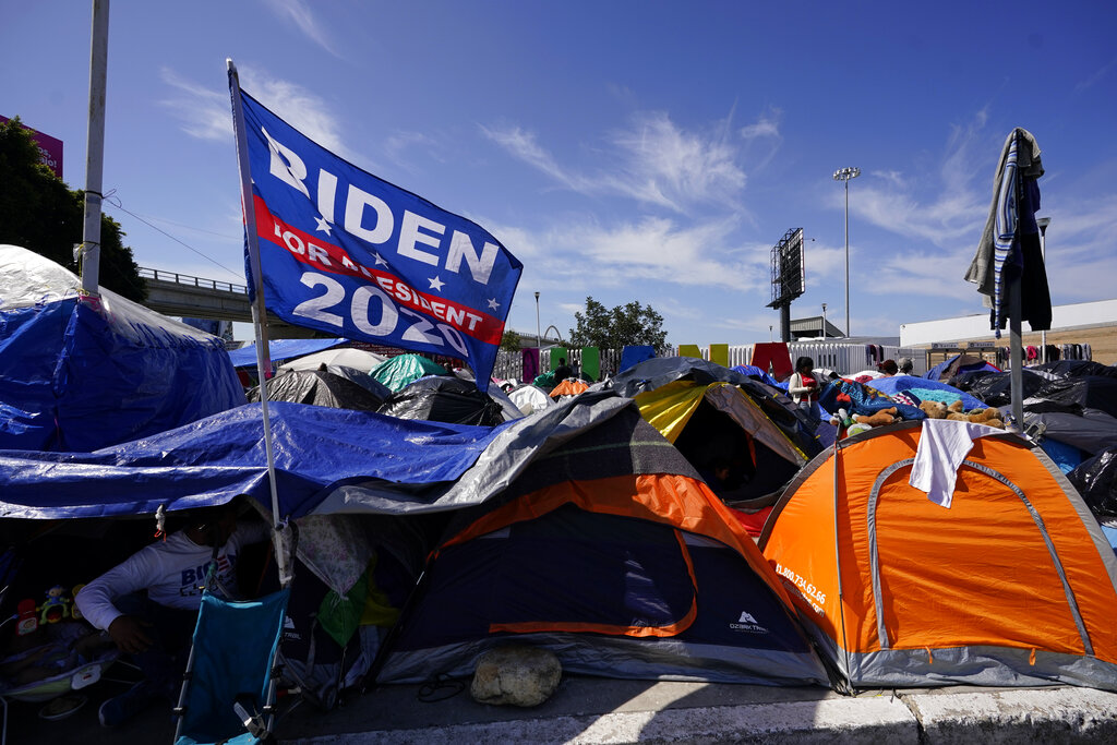 A donated campaign flag for U.S. President Joe Biden flies over tents at a makeshift camp of migrants at the border port of entry leading to the United States, Wednesday, March 17, 2021, in Tijuana, Mexico. The migrant camp shows how confusion has undercut the message from Biden that it's not the time to come to the United States. Badly misinformed, some 1,500 migrants who set up tents across the border from San Diego harbor false hope that Biden will open entry briefly and without notice. (AP Photo/Gregory Bull)