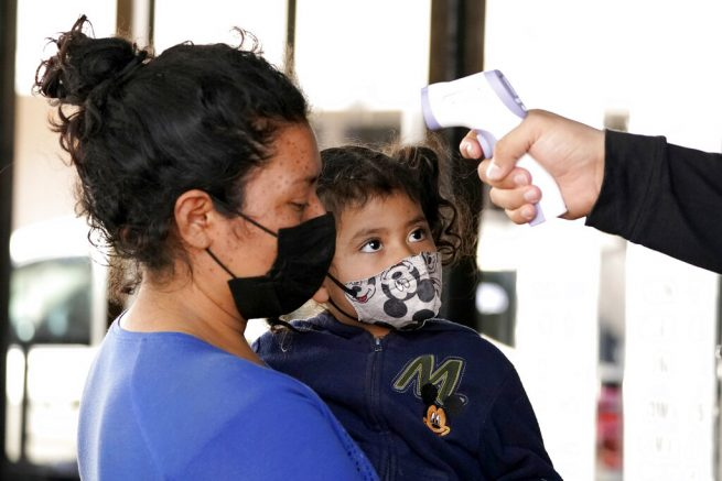 A migrant's temperature is taken at the entrance of a respite center as a child looks on after they were taken into custody and released from U.S. Customs and Border Protection while trying to sneak into the U.S., Friday, March 19, 2021, in McAllen, Texas. A surge of migrants on the Southwest border has the Biden administration on the defensive. The head of Homeland Security acknowledged the severity of the problem Tuesday but insisted it's under control and said he won't revive a Trump-era practice of immediately expelling teens and children. (AP Photo/Julio Cortez)