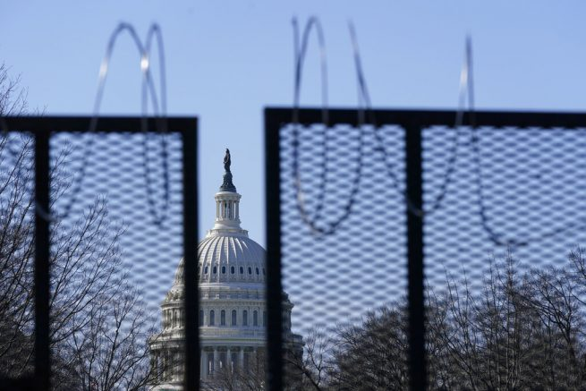 The U.S. Capitol dome stands past partially-removed razor wire hanging from a security fence on Capitol Hill in Washington, Saturday, March 20, 2021. (AP Photo/Patrick Semansky)